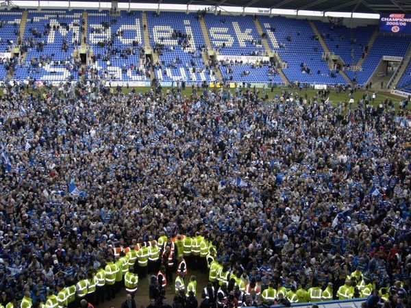 Reading Fans celebrate winning the Championship title on the pitch after Reading's 5-0 defeat of Derby County