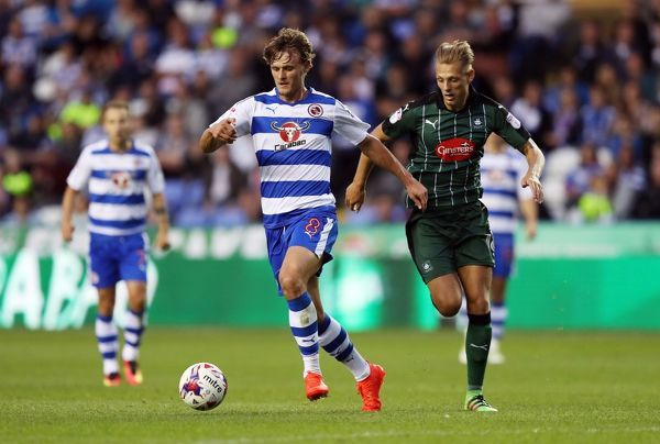 Reading's John Swift (centre) and Plymouth Argyle's Oscar Threlkeld battle for the ball during the first round match of the EFL Cup at the Madejski Stadium, Reading